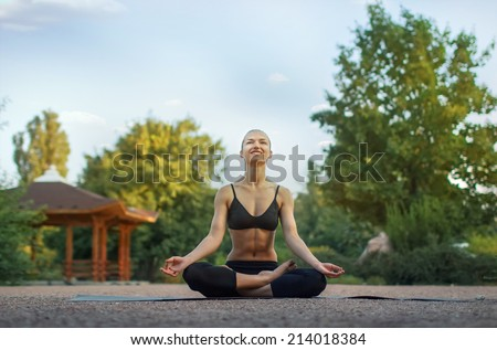 Good morning with yoga.Beautiful young caucasian woman in fitness wear doing exercises in a park - stock photo