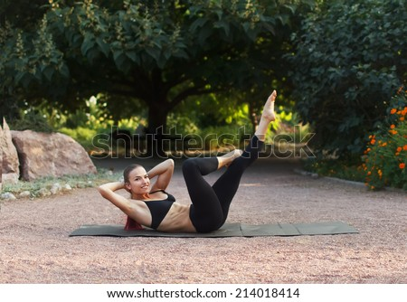 Good morning with yoga.Beautiful young caucasian woman in fitness wear doing exercises in a park.Abdominal exercises - stock photo