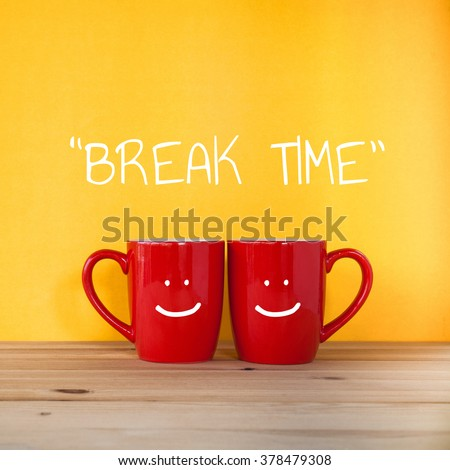 Good morning word.Two cups of coffee and stand together to be heart shape on yellow background with smile face on cup. - stock photo
