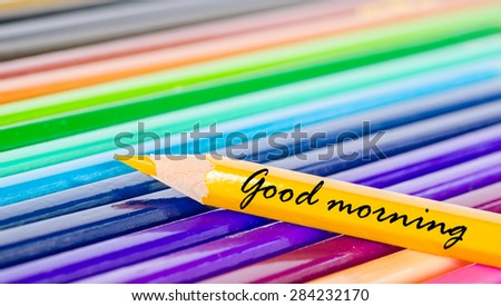 Good morning wording with yellow pencil on many color pencils background. - stock photo