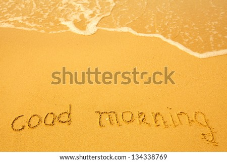 Good morning - written in sand on beach texture.