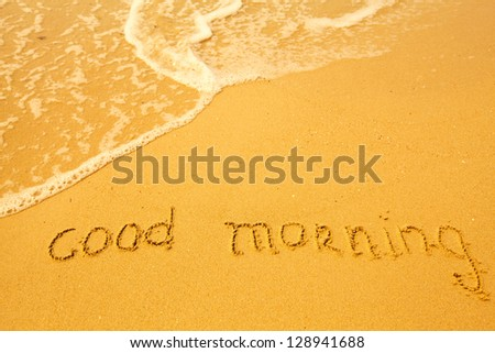 Good morning - written in sand on beach texture - soft wave of the sea - stock photo