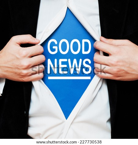 Good news. Businessman showing a superhero suit underneath his shirt with a message text written on it. - stock photo