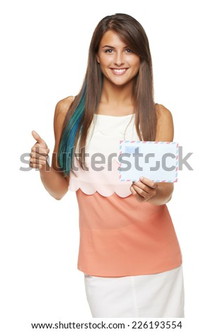 Good news concept. Trendy young smiling woman giving you blank envelope and gesturing thumb up, over white background. Shallow depth of field, focus on envelope - stock photo