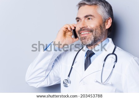Good news. Confident mature grey hair doctor talking on the mobile phone and smiling while standing against grey background