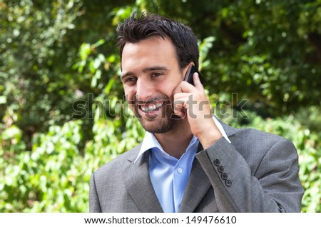 Good news for the businessman in the park  - stock photo