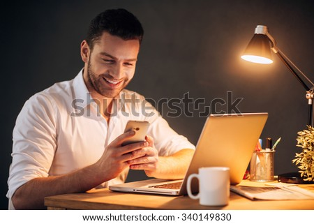 Good news from colleague. Confident young man looking at his smart phone and smiling while sitting at his working place at night time - stock photo