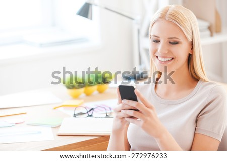 Good news from colleagues. Beautiful young woman holding mobile phone and smiling while sitting at her working place in office