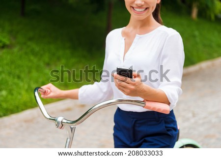 Good news from friends. Close-up of young woman holding mobile phone and smiling while walking with her bicycle in park