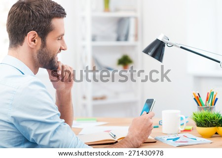 Good news from friends. Side view of handsome young man holding mobile phone and looking at it with smile while sitting at his working place - stock photo