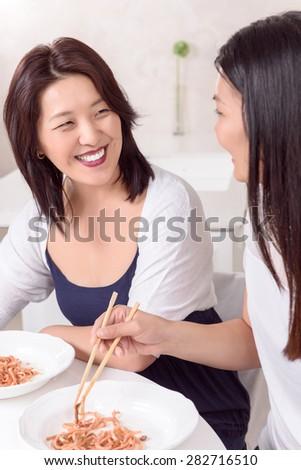 Good news. Happy Asian girls eating Asian food at home - stock photo