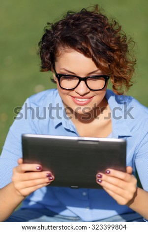 Good news. Pretty appealing contented young girl holding laptop and expressing joy while having rest on the grass - stock photo