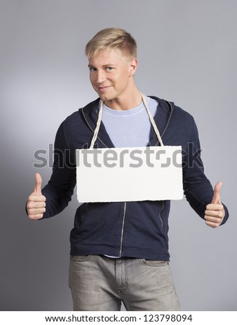 Good news: Smiling man giving thumbs up at white blank signboard with space for text isolated on grey background. - stock photo