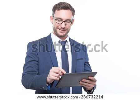 Good news. Smiling vivacious bearded businessman holding laptop and keeping his eyes down while surfing through the Internet.