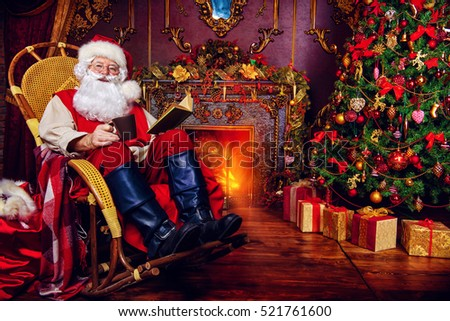 Good old Santa Claus having a rest in his house next to the fireplace and Christmas tree.