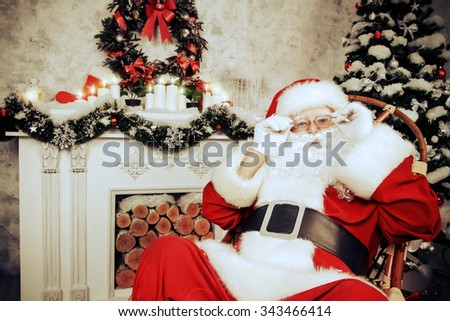Good old Santa Claus sitting in a rocking chair in the room by the fireplace and Christmas tree, beautifully decorated for Christmas. Retro style. - stock photo