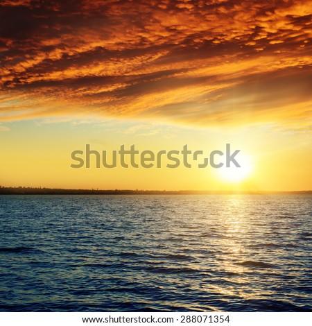 good red sunset over darken water - stock photo