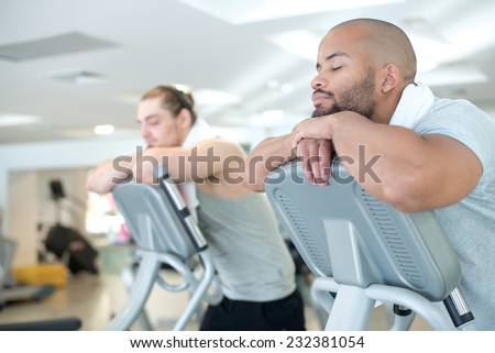Good rest after good workout. Two handsome guys are having rest after great sport workout on treadmill in a gym. Both sportsmen are standing on a treadmill - stock photo