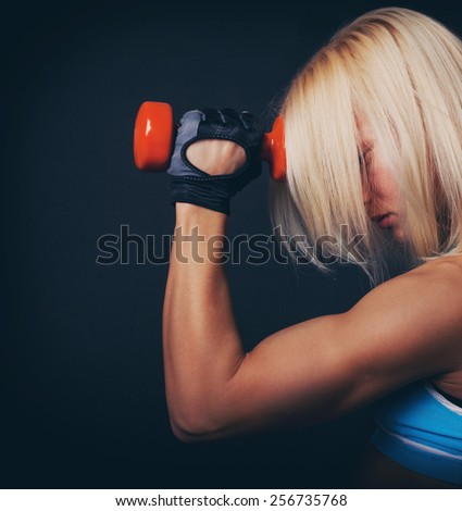 Good-shaped athletic girl stands and holds dumbbell - stock photo