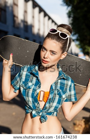 good shaped beautiful girl in blue knot checked shirt holds a skateboard