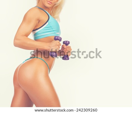 Good-shaped sexy athletic girl poses and holds dumbbells - stock photo