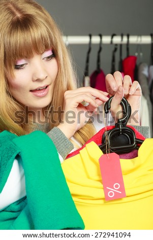 Good shopping sale concept. Blonde fashionable woman choosing clothes holding discount red label with percent sign in hand - stock photo