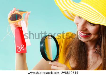 Good shopping summer sale concept. Fashionable woman choosing sunglasses searching through magnifying glass, discount red label with percent sign in hand - stock photo
