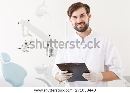 Good specialist. Portrait of handsome dentist with beard standing on background of stomatology clinic holding folder.