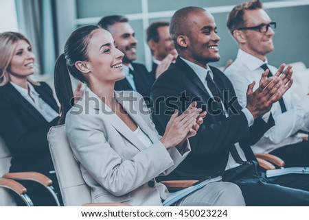 Good speech. Group of happy business people in formalwear sitting at the chairs in conference hall and applauding - stock photo
