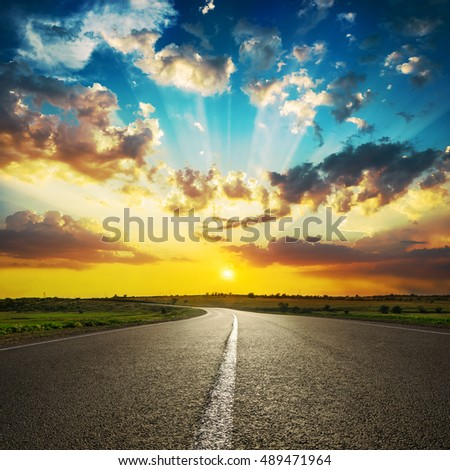 good sunset in clouds and asphalt road