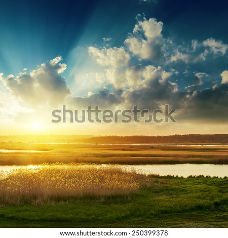 good sunset with clouds over river - stock photo