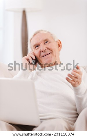 Good talk. Happy senior man talking on the mobile phone and holding laptop on his knees while sitting in chair at his apartment - stock photo