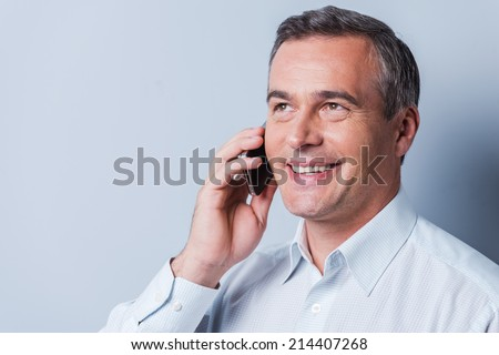 Good talk. Portrait of confident mature man in shirt talking on the mobile phone and smiling while standing against grey background - stock photo