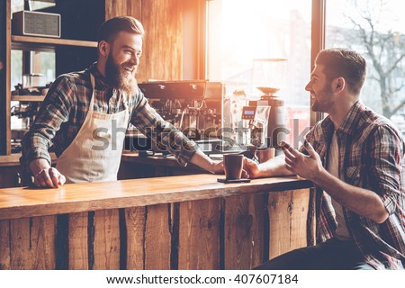 Good talk with customer. Barista and his customer discussing something with smile while sitting at bar counter at cafe - stock photo