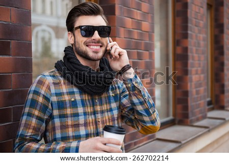 Good talk with friend. Cheerful young man holding coffee cup and talking on the mobile phone while standing at the street  - stock photo