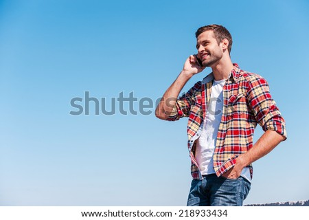 Good talk with friend. Cheerful young man talking on mobile phone and smiling while standing outdoors with blue sky as background  - stock photo