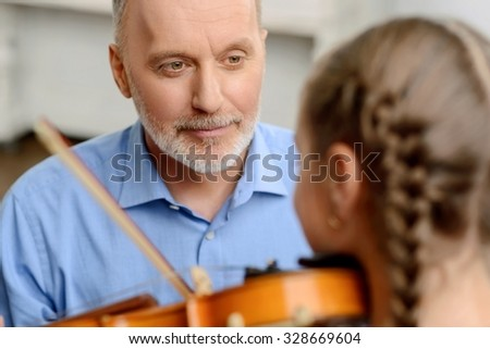 Good teacher. Selective focus of pleasant adult man looking at little girl who plays the violin while having music lesson - stock photo