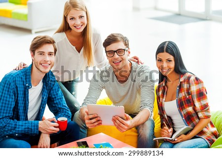 Good team is a key to success. Group of happy young people working together while sitting in the rest area of their office - stock photo