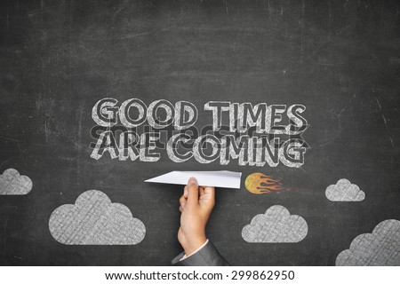 Good times are coming concept on black blackboard with businessman hand holding paper plane - stock photo