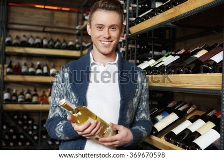 Good wine for good mood. Young handsome male customer smiling happily posing in a wine store cellar