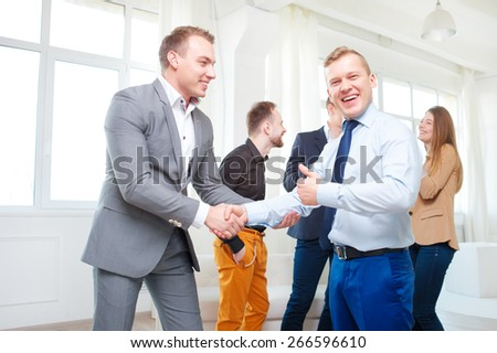 Good work! Two confident businessmen shaking hands with colleagues talking in the background. Indoors.