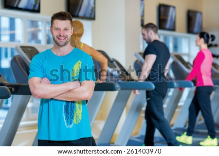 Good workout and sport confidence. Portrait of young and handsome sports looking man. Man is looking in the camera with confidence, treadmills training is on the background