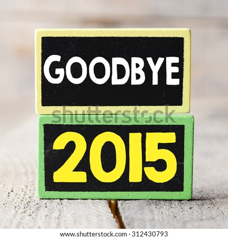 Goodbye 2015 year on blackboards on wooden background