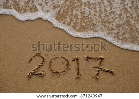 Goodbye 2017 years. Hand writing 2017 on sand beach with wave is coming. New year concept