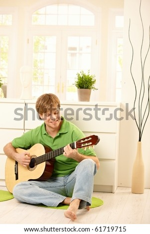 Goodlooking guy playing guitar in bright living room.? - stock photo