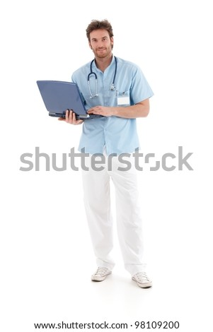 Goodlooking young doctor working on laptop, smiling at camera. - stock photo