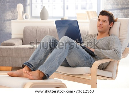 Goodlooking young man relaxing at home in armchair, sitting in living room with laptop computer, smiling.?