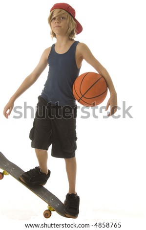 Goofing around -- Caucasian boy of ten with long blond hair holds basketball under one arm and stands balanced on end of skateboard