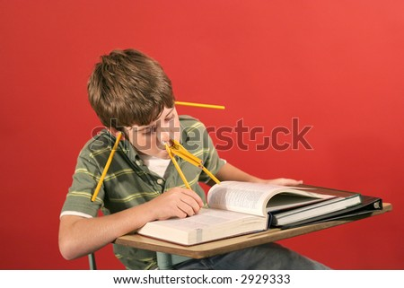 goofy kid studying with pencils - stock photo