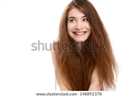 Goofy woman smiling looking to the side, long brown not brushed hair. - stock photo